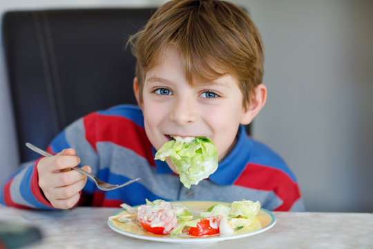 Happy kid boy eating fresh salad with tomato, cucumber and different vegetables as meal or snack. Healthy child enjoying tasty and fresh food at home or at school canteen.