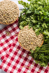 Uncooked lentils in wooden bowles  with parsley herbs on kitchen table