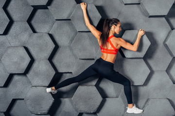 Fit woman posing like a climber hanging on decorative wall Wall mural
