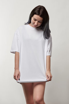 beautiful young woman in white oversize t-shirt with copy space isolated on grey