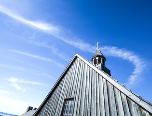 Church Steeple And Blue Sky Copy Space. Side of wooden church with steeple and cross set against a blue sky with copy space.