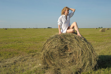 woman in a white shirt on a haystack