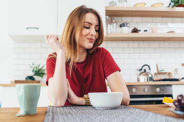 Young beautiful woman eating fruits and vegetables healthy food in kitchen.