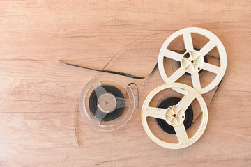 Old vintage cinematic reels of white color and transparent with a video film lie on the background of the Kraft surface. Top view.