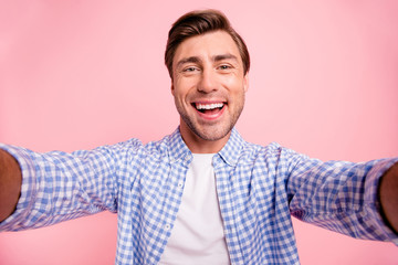 Close up photo of beautiful amazing brunet he him his handsome hold telephone in arms make take selfie wear casual checkered plaid shirt outfit isolated on rose background