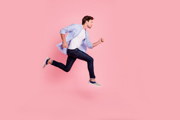 Full length side profile body size photo of jumping high he his him handsome run fast  look empty space need win victory winner wearing casual jeans checkered plaid shirt isolated on rose background Wall mural