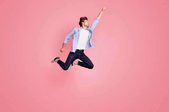 Full length body size photo of jumping high he his him I save world handsome flight up fist raised superman pose shape mood wearing casual jeans checkered plaid shirt isolated on rose background