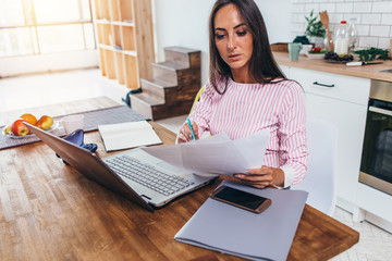 Woman working with documents and laptop in the kitchen at home