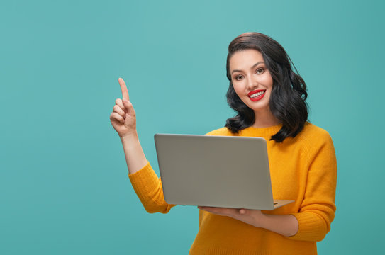 woman with laptop on teal background