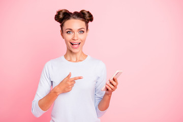 Portrait of her she nice attractive lovely sweet cheerful cheery positive girl holding cell in hands pointing at notification isolated over pastel pink background