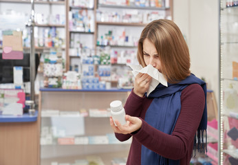 Woman using tissue in drugstore and holding pills bottle.