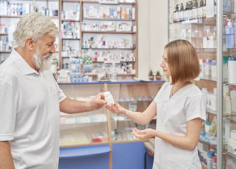 Old man consulting with pharmacist in drugstore.