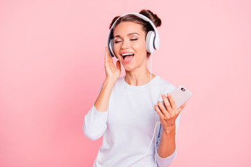 Portrait of nice lovely winsome fascinating attractive cheerful cheery dreamy girl wearing touching earphones closed eyes loud melody isolated over pink pastel background