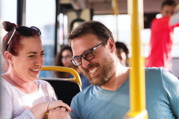 Happy middle-aged Couple holding hands while sitting and driving in city bus.