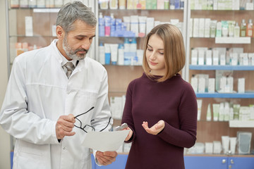 Pharmacist consulting woman about prescription in pharmacy.
