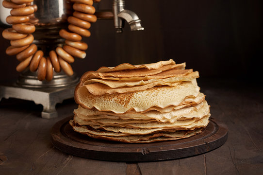 A traditional water boiler pot Russian Samovar with stack of thin pancakes blini
