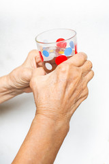 Senior woman's hand holding polka dot glass, drinking water on white background