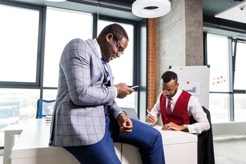 African businessman sitting with a phone on the table with a colleague in the office