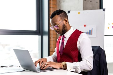 Stylish African businessman in a suit working at a laptop at a table in a modern office