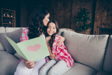 Close up photo two people mum little daughter giving postcard with mommy poem kissing sweet girl unexpected cute delighted wear pink plaid shirts flat apartment room sit cozy couch sofa divan