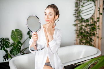 Beautiful woman taking care of herself, looking into the mirror with a serious facial expression in the bathroom