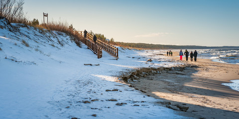 Seascape with snow covered sandy beach, dunes and wooden path leading to Carnikava promenade. Latvia. Baltic.