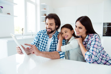 Portrait of nice cute lovely attractive tender cheerful cheery people mom dad spending time having fun using gadget device in light white modern interior indoors