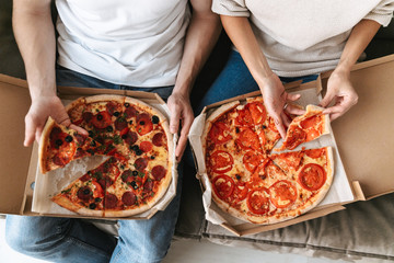 Top view of a couple eating two big pizzas