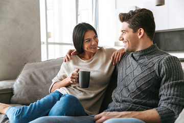 Happy young couple sitting on a couch at home