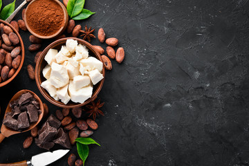 White Chocolate and Cocoa Beans. On a black background. Top view. Free copy space.