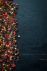 Red and black pepper on a wooden background. Spices Top view. Free space for your text.