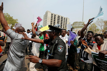 Nigerian police officer tries to disperse protesters, some supporting and some opposing the suspension of the Chief Justice of Nigeria Walter Onnoghen, in Abuja