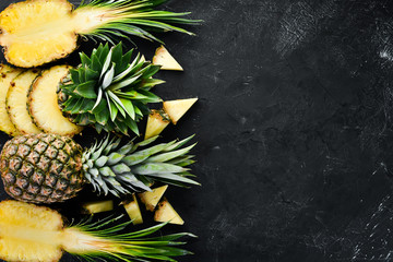 Sliced pineapple on a black background. Tropical Fruits. Top view. Free copy space.