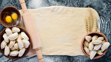 Dumplings with potatoes. Vareniki Homemade. Flour, eggs, dough on a black background. Top view. Free copy space.
