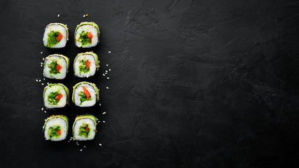 Sushi roll with avocado, cucumber and tomato. Japanese cuisine. Top view. On a black background.