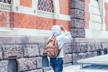 Black guy in a gray hoodie with hood walking on city street