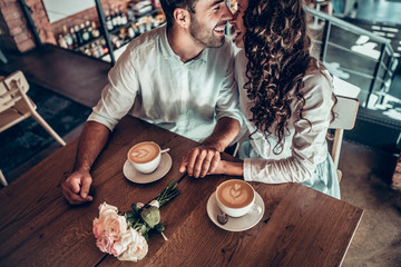Sincere feelings. A couple in love is enjoying each other sitting in a cafe and drinking coffee.