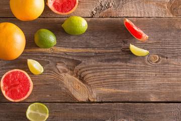 Set of sliced citrus fruits over wooden background