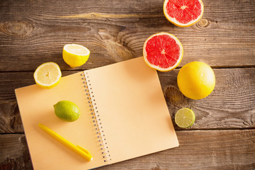 citrus with notebook on old wooden table
