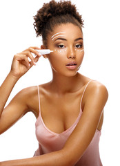 Face lifting. Beautiful woman using rejuvenating cream. Photo of african american woman with perfect skin on white background. Skin care and beauty concept