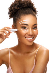 Face lifting. Beautiful smiling woman using  rejuvenating cream. Photo of african american woman with healthy skin on white background. Skin care and beauty concept