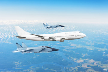Large passenger plane, accompanied by two military fighter. Concept of airborne danger, air force.