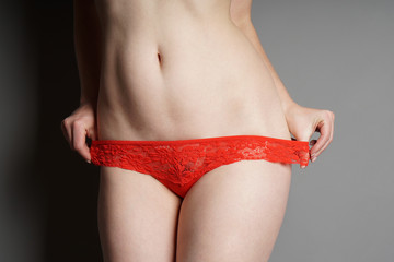 unrecognizable young woman pulling down red lace panties - striptease or seduction concept