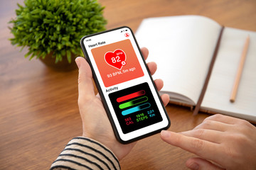 female hands holding phone with app heart and activity