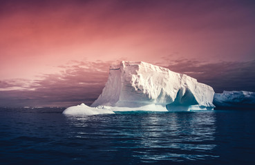 The huge iceberg on the colorful sunset sky background. Breathtaking magic Antarctic landscape. The ice and snow covered glacier floating among the frozen polar ocean. Overwhelming fairy tale scene.