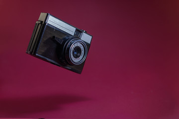 Old retro camera on red background flying in air.
