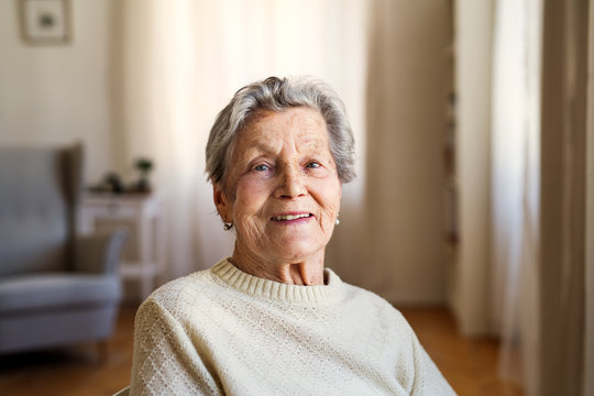 A portrait of a senior woman sitting at home, looking at camera.