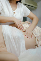 Close to the female hands of a massage therapist makes a light massage to the belly of a pregnant girl in a cosmetology room