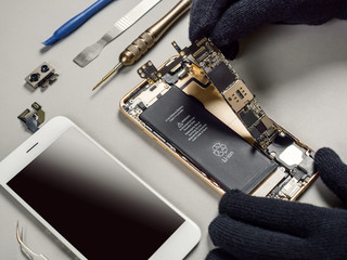 Technician or engineer disassembling components broken smartphone and take off logic board for repair or replace new smartphone logic board on desk