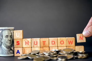 Human hand putting USA shutdown wording on wooden cubes and US dollar banknote and coins on black background. United States of America Government shutdown concept.Image